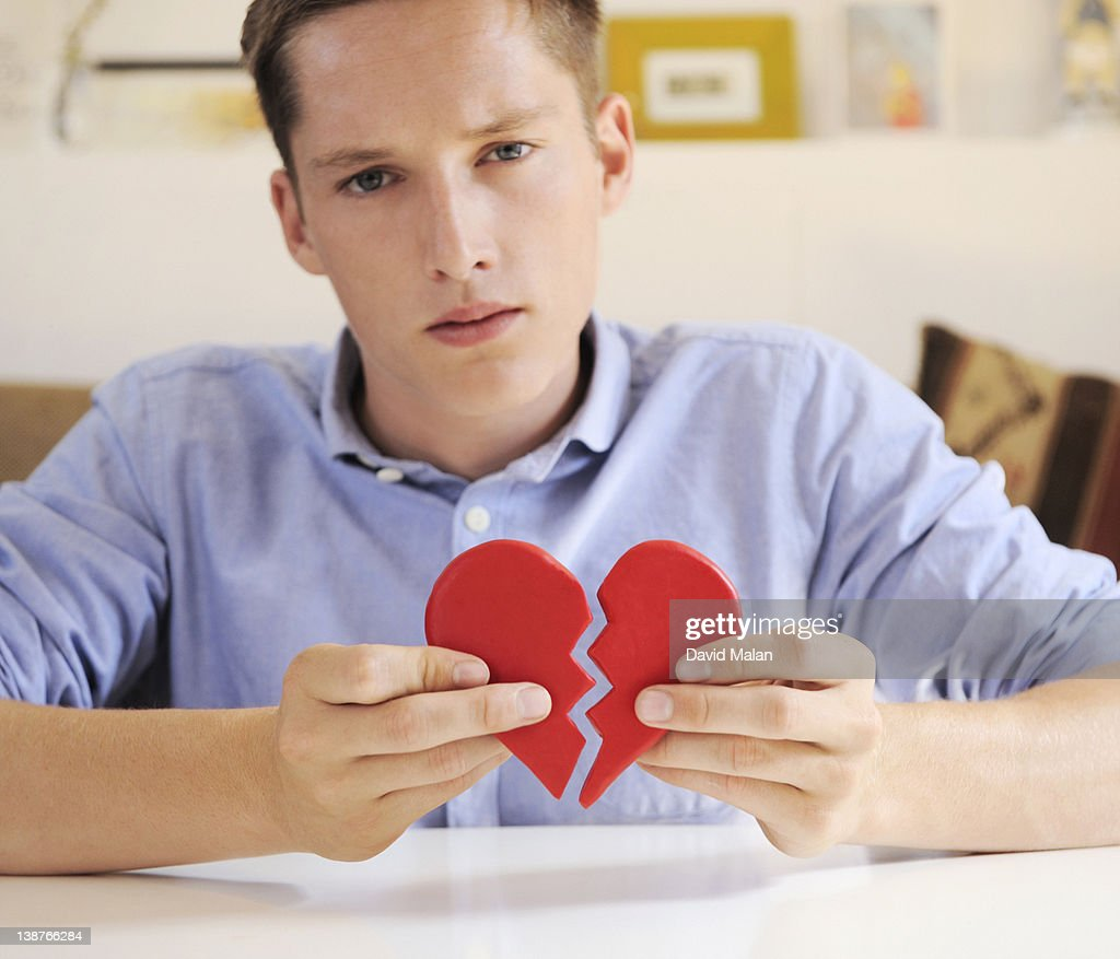 Young Man Holding A Broken Heart Stock Photo