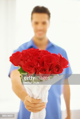 young man holding a bunch of flowers : Stock Photo
