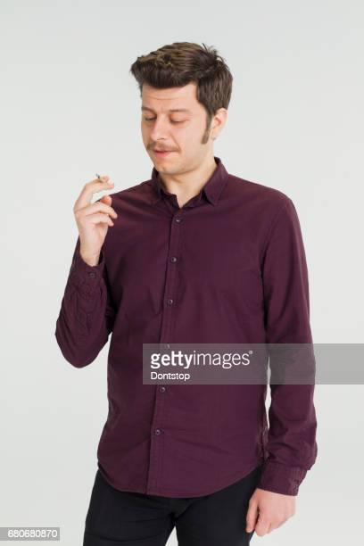 Young man holding a cigarette in his hand