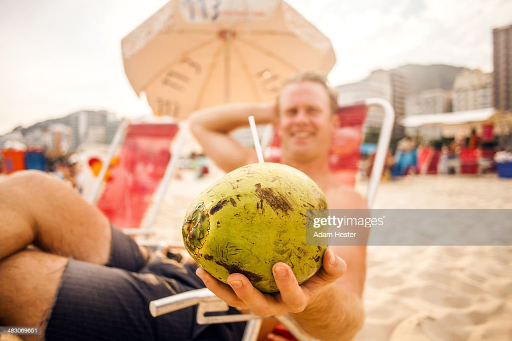 A young man holding a coconut on Copacabana Beach.