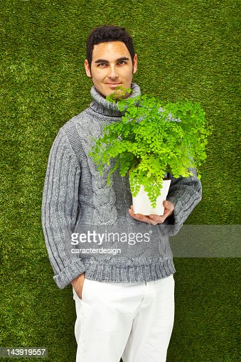 Young man holding a fresh plant, thinking green