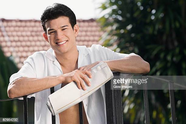 Young man holding a newspaper and smiling