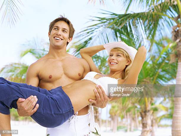 Young man holding a Young woman on a beach