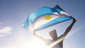 Young man holding argentinian national flag to the sky with two hands at the beach at sunset