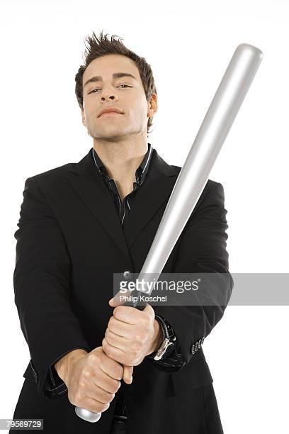 'Young man holding baseball bat, close-up'