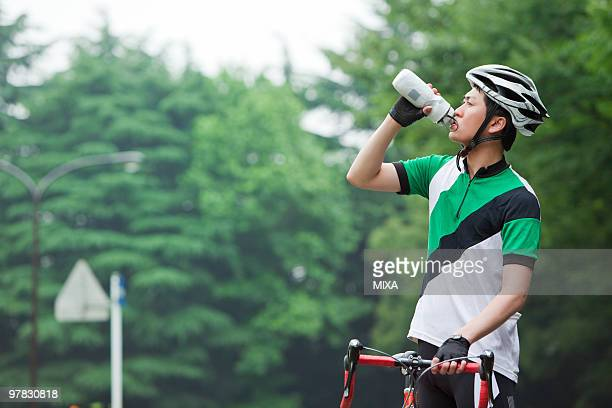 Young man holding bicycle and drinking