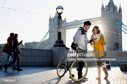 Young man holding bicycle with woman at Tower Bridge, London, England : Stock Photo