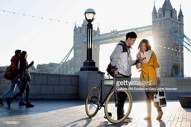 Young man holding bicycle with woman at Tower Bridge, London, England
