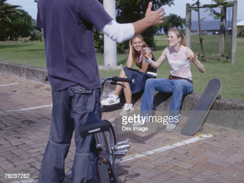 Young man holding bike talking to young women sitting on curb : Stock Photo
