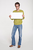 Young man holding blank white board, portrait