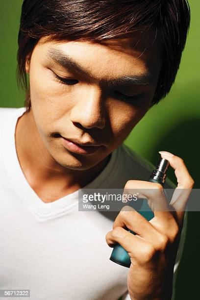 Young man holding bottle of perfume