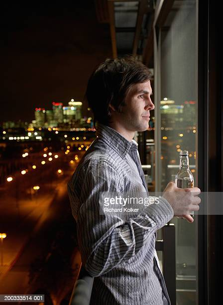 Young man holding bottle on balcony, night, side view