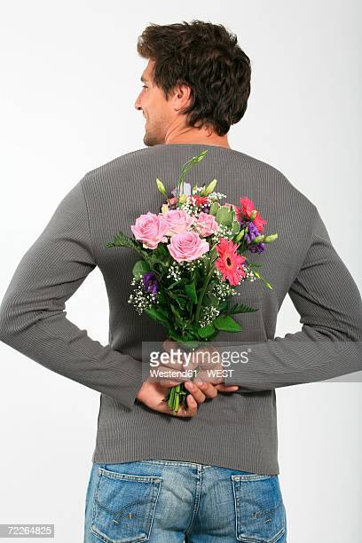 Young man holding bouquet of flowers behind back, smiling, rear view