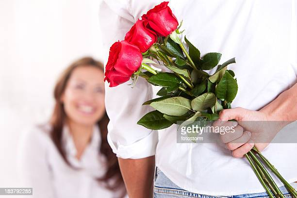 Young man holding bouquet of red roses behind back