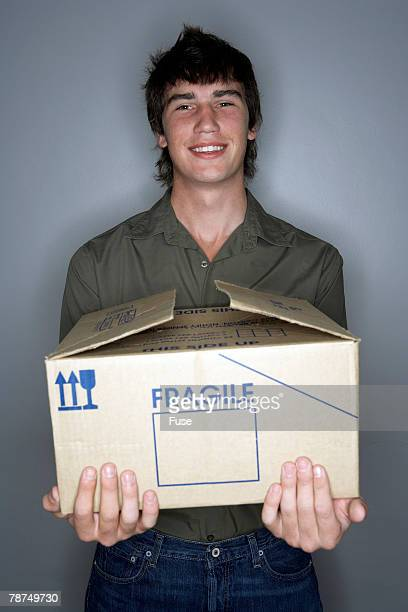 Young Man Holding Box Marked Fragile