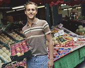 Young man holding box of fruit by market stall, smiling, portrait