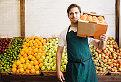 Young man holding box of oranges at market stall, portrait