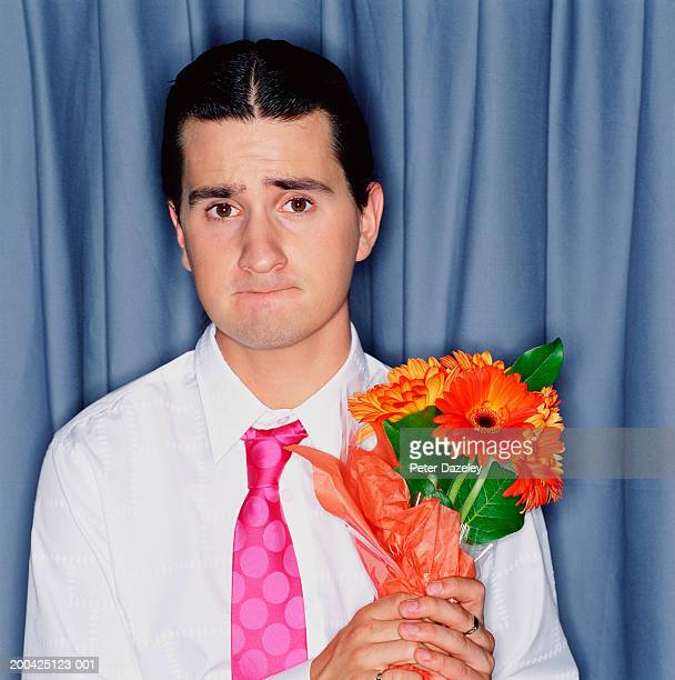 Young man holding bunch of gerberas, biting bottom lip, portrait