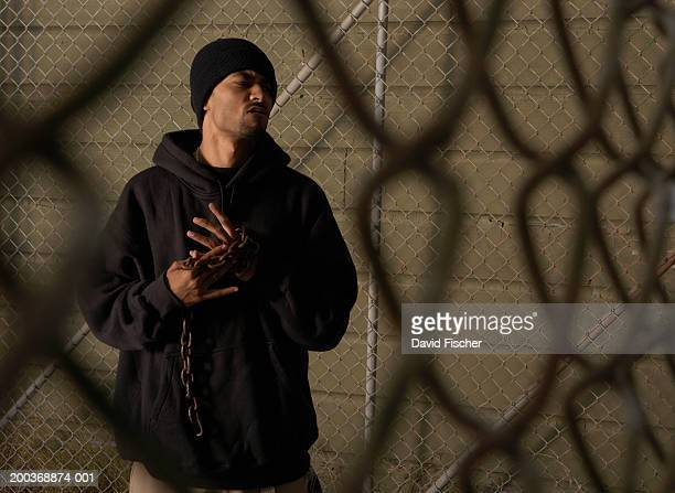 Young man holding chain beside chainlink fence, frowning, night