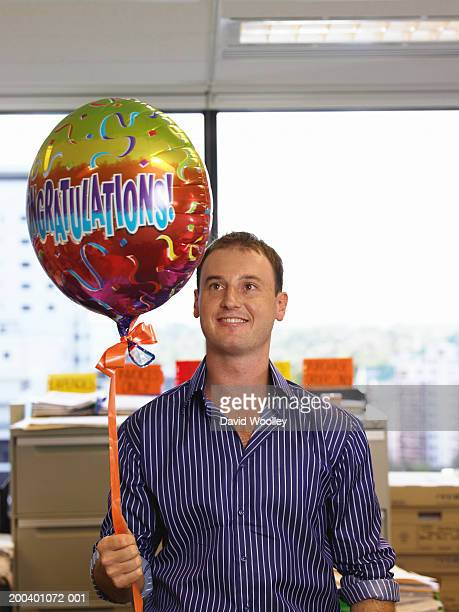 Young man holding 'congradulations' balloon in office, smiling
