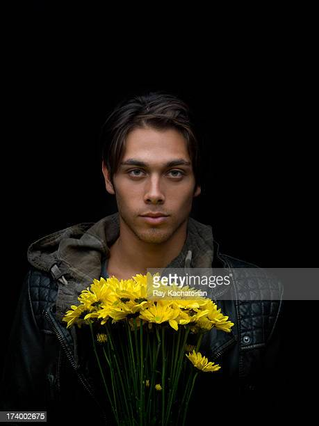 Young man holding daisies