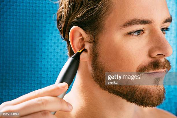 Young man holding ear trimmer.