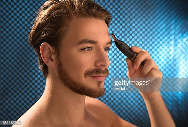 Young man holding eyebrow trimmer.