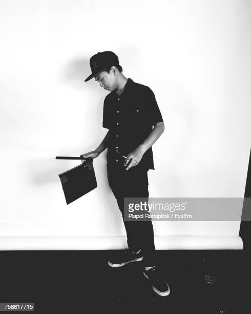 Young Man Holding Film Slate While Standing Against Wall