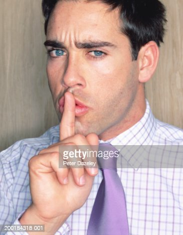 Young man holding finger to lips, portrait : Stockfoto