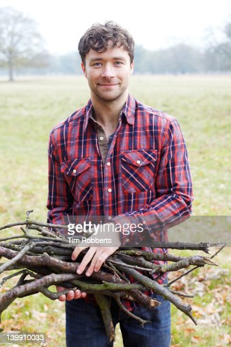 Young man holding firewood.