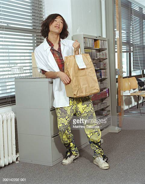 Young man holding food delivery in office