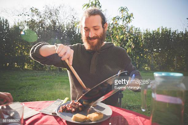 Young man holding frying pan serving food