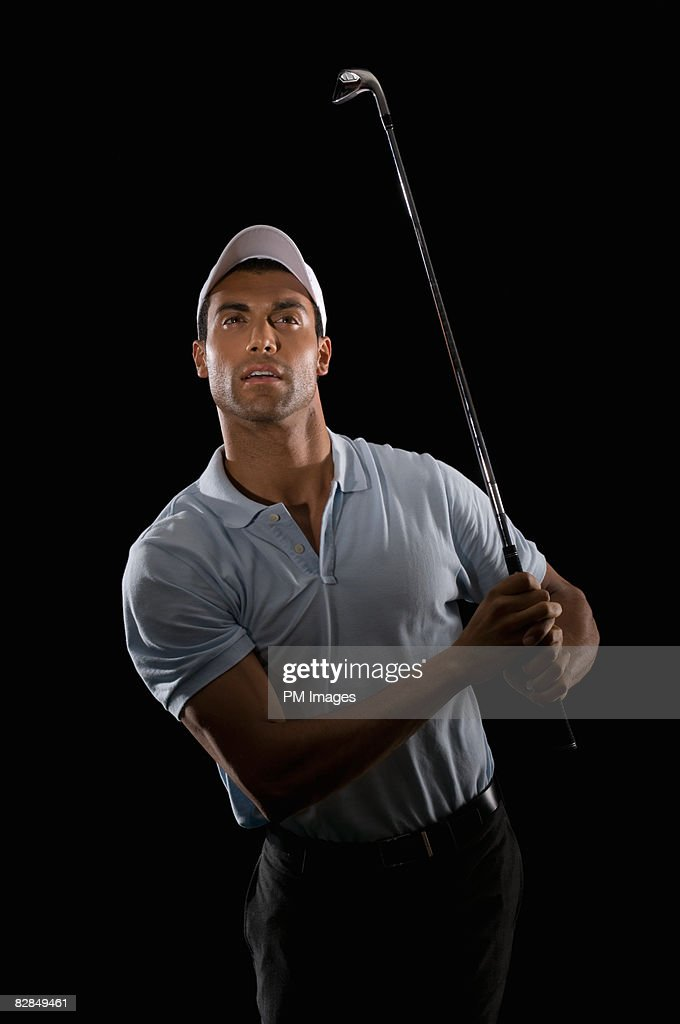 Young man holding golf club, looking into distance : Stock Photo