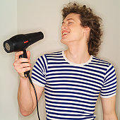 Young man holding hair dryer to face, smiling