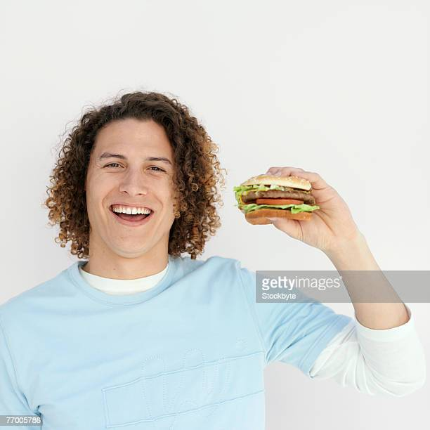 Young man holding hamburger and laughing, portrait, upper half