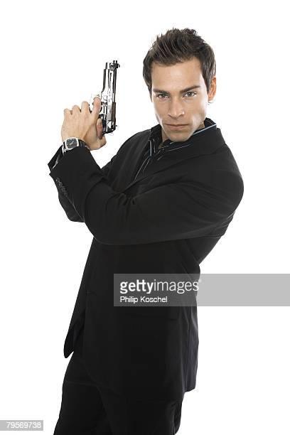 'Young man holding hand gun, close-up'