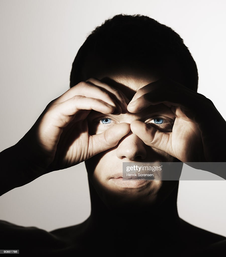 young man holding hands like binoculars : Stock Photo