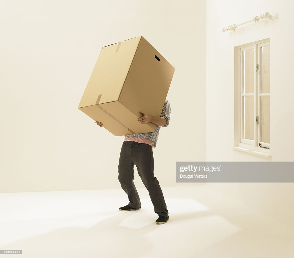 Young man holding heavy box. : Stock Photo