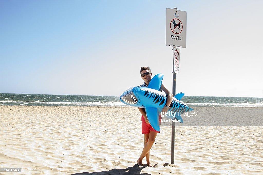 Young man holding inflatable tiger shark, Port Melbourne, Melbourne, Australia
