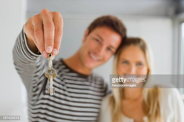 Young man holding keys and woman standing together