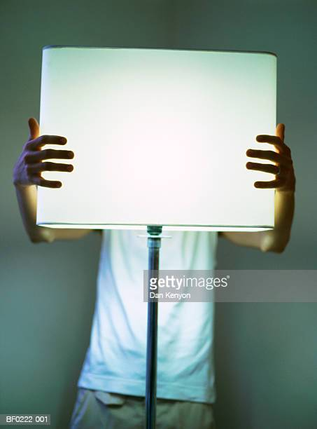 Young man holding lampshade, close-up