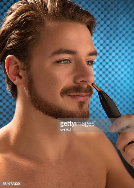 Young man holding nose trimmer.