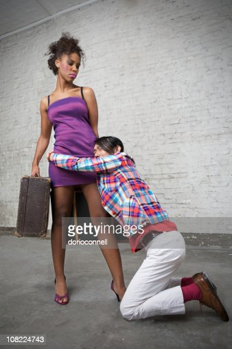 Young Man Holding On To Woman Leaving with Luggage : Stock Photo