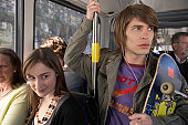 Young man holding onto railing on bus