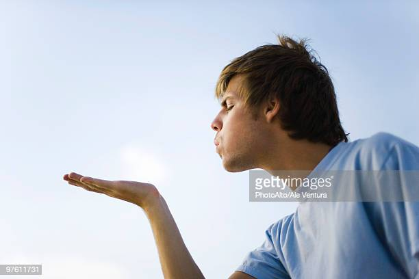 Young man holding out palm, blowing, eyes closed