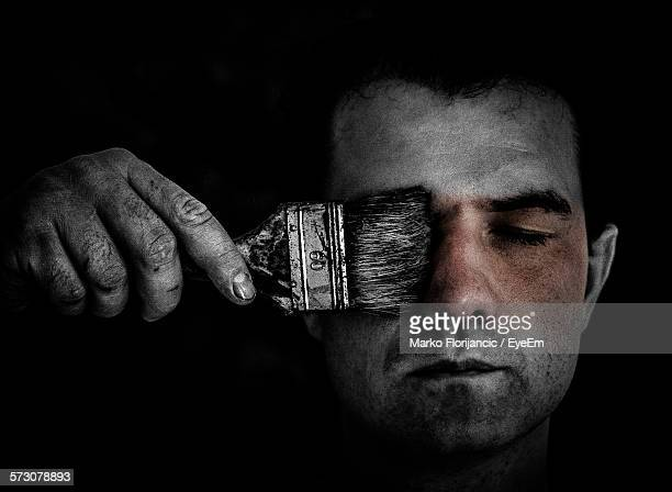 Young Man Holding Paint Brush Over Closed Eyes Against Black Background