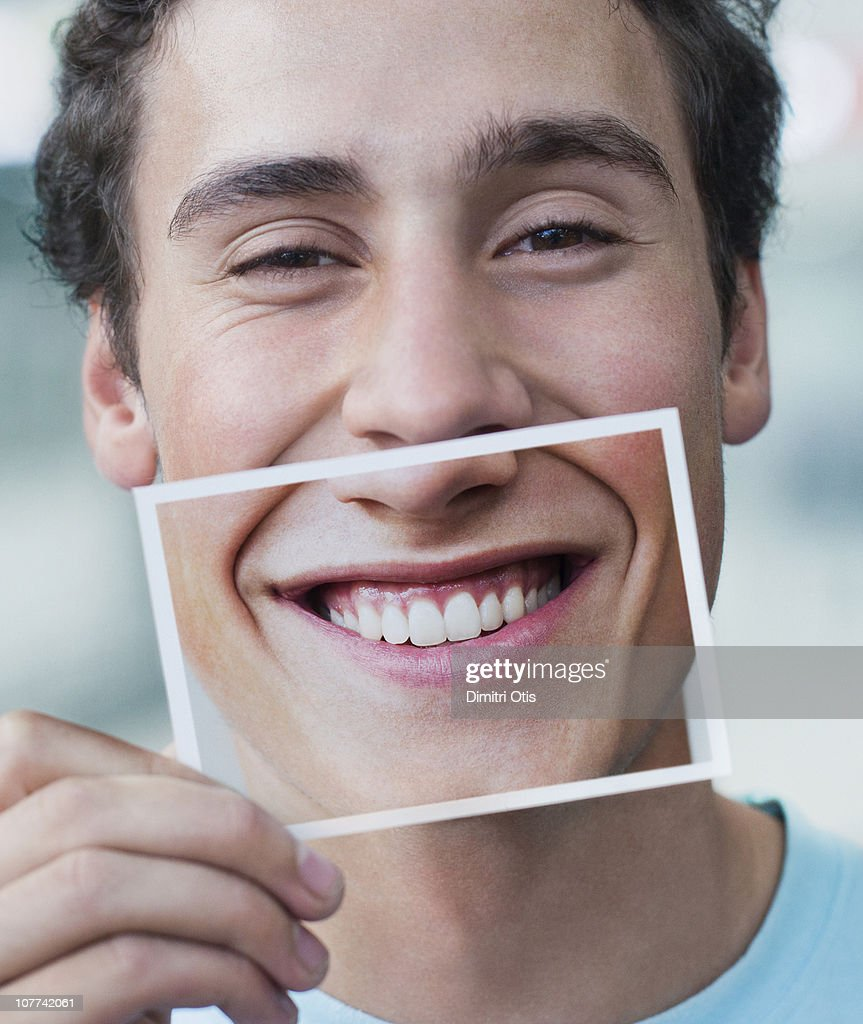 Young man holding picture of his smile