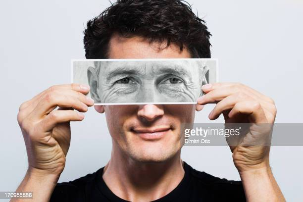 Young man holding picture of old eyes over his