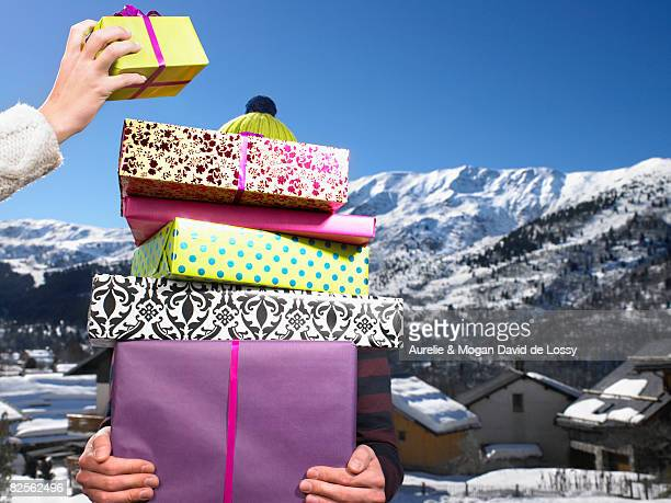 Young man holding pile of presents