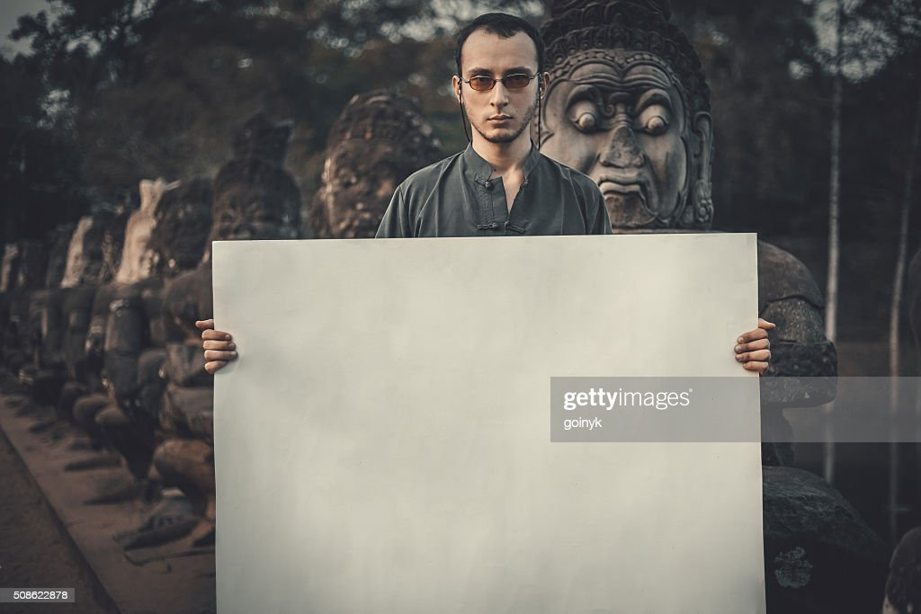 Young man holding placard : Stock Photo